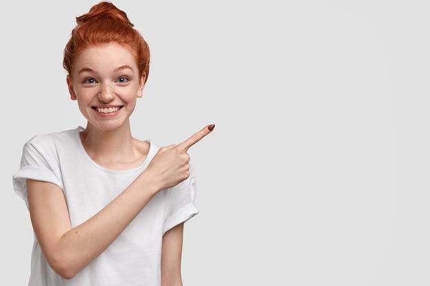 Positieve charmante roodharige vrouw toont haar huis, wijst met wijsvinger opzij, blij en stelt voor kopie ruimte te gebruiken, nonchalant gekleed, modellen