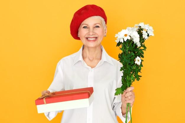 Positieve charmante vrouw van middelbare leeftijd die verjaardagscadeau ontvangt, verjaardag viert, met bos witte madeliefjes en snoepdoos, camera kijkt met een stralende, gelukkige glimlach. viering concept