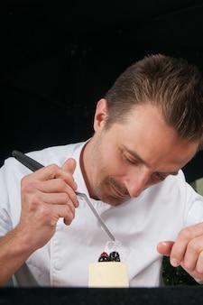 Positieve chef-kok versieren van ijs met bessen