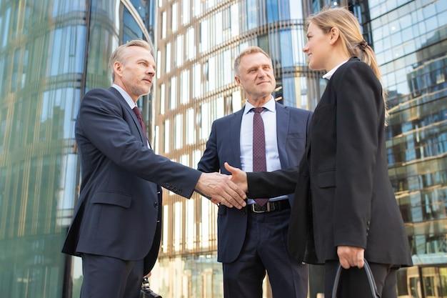 Positieve collega's ontmoeten elkaar in de stad, staan buiten en schudden handen in de buurt van kantoorgebouw. lage hoek geschoten. overeenkomst en partnerschap concept
