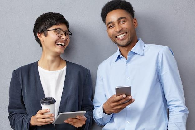 Positieve collega's van gemengd ras werken met moderne tablets en smartphones
