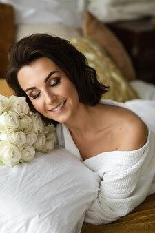 Positieve dame in badjas met make-up op haar ogen glimlachend terwijl u ontspant op het bed met een boeket witte rozen.