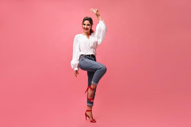 Positieve dame in denim outfit toont vredesteken op roze achtergrond. gelukkige jonge vrouw in goed humeur in witte blouse glimlachen.