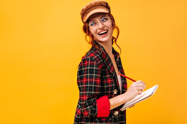 Positieve dame in geruite outfit en pet poseert met notitieboekje op geïsoleerde muur