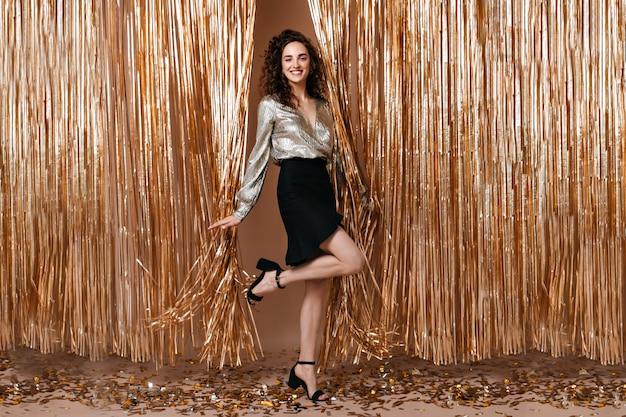 Positieve dame in zwarte rok en glanzende bovenkant die koket been op gouden achtergrond opheft
