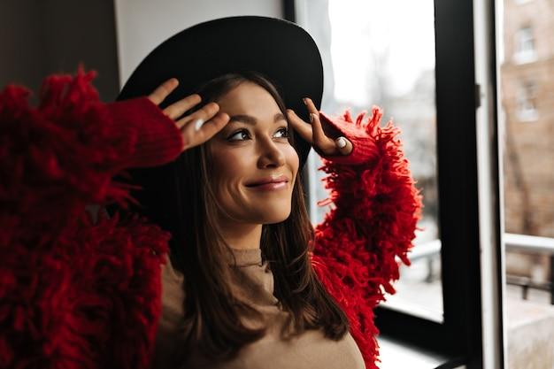 Positieve dame met glans op haar lippen in goed humeur kijkt uit raam. foto van vrouw in rode eco jas en hoed.