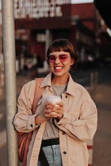 Positieve dame met kort haar trekt grappig gezicht op straat