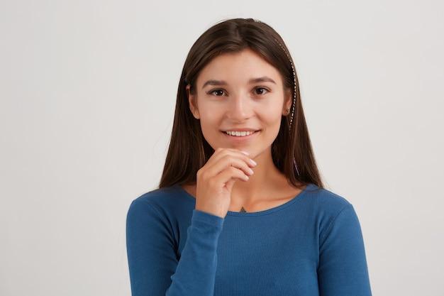 Positieve dame, mooie vrouw met donker lang haar, gekleed in een blauwe trui