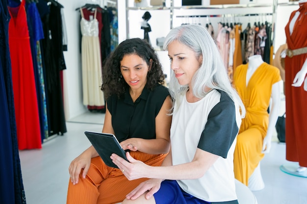 Positieve dames die samen zitten en tablet gebruiken, kleren en aankopen in modewinkel bespreken. consumentisme of winkelconcept