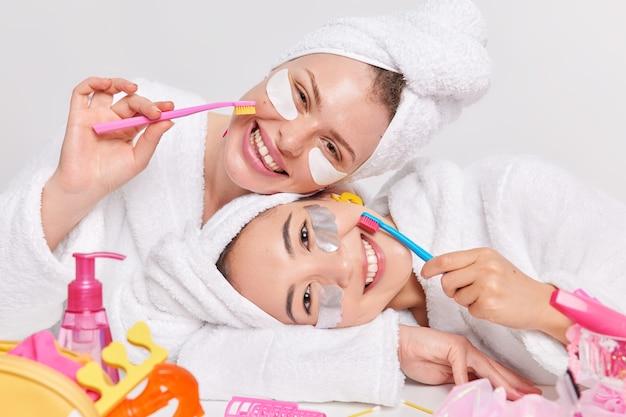 Positieve diverse jonge vrouwen kantelen hoofden glimlachen aangenaam verzorgen van teint en tanden houden tandenborstels gekleed in zachte badjassen handdoeken over hoofden ondergaan schoonheids- en hygiëneprocedures