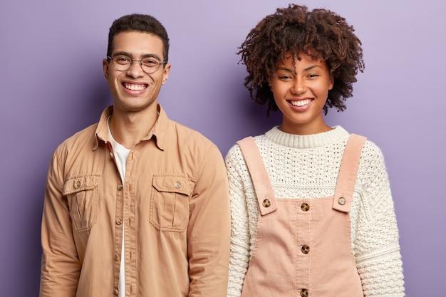 Positieve diverse studenten hebben een brede glimlach, tonen goede emoties, staan dicht bij elkaar, maken graag de opdracht aan huis af, dragen modieuze kleding, geïsoleerd over een paarse muur. emoties concept
