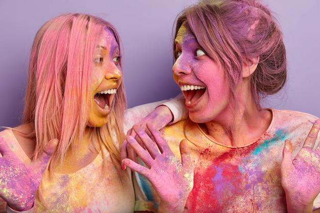 Positieve dolgelukkige europese vrouwen kijken elkaar vrolijk aan, roepen uit en hebben samen plezier, vuil van holi-kleuren, staan over de paarse muur, zijn erg emotioneel en tevreden. lente vakantie