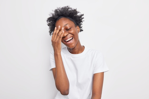 Positieve donkere gekrulde vrouw glimlacht breed houdt hand op gezicht lacht oprecht