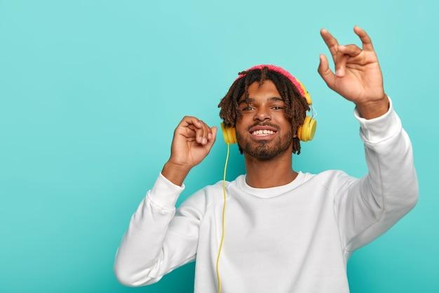 Positieve donkere hipster kerel gebruikt moderne koptelefoon voor het luisteren naar muziek, geniet van perfect geluid, breed glimlachen, dansen tegen blauwe muur