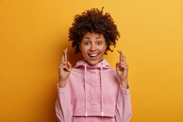 Positieve donkere huid jonge vrouw met afro kapsel ziet er hopelijk uit
