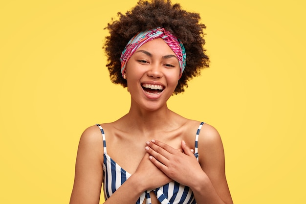 Positieve donkere jonge vrouw met een tevreden uitdrukking, voelt zich tevreden om compliment of bekentenis in liefde te horen, houdt beide handen op de borst