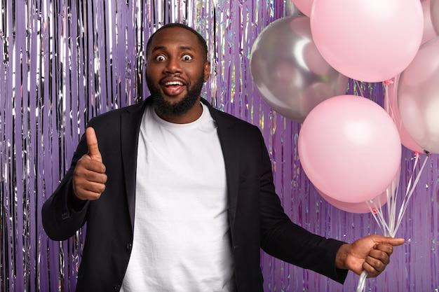 Positieve donkere man geeft dreun op, houdt van een briljant idee van het organiseren van een feest, houdt een heleboel luchtballonnen vast, heeft wijd geopende ogen, viert een speciale gelegenheid