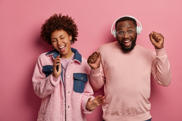 Positieve donkere vrouw en man dansen vreugdevol met het ritme van muziek, gebalde vuisten, zingen in smartphoneapparaat