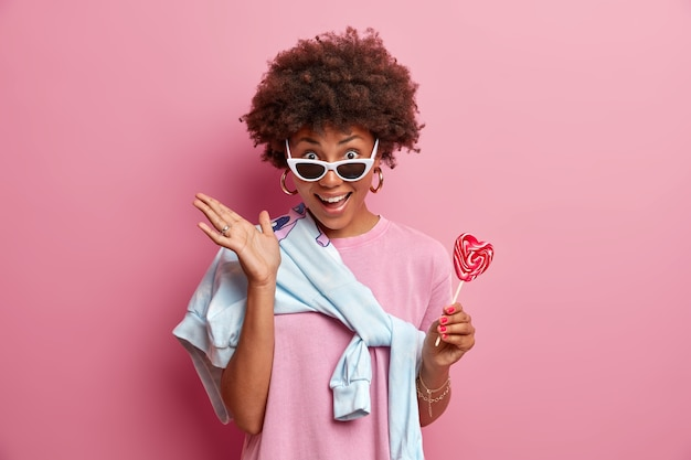 Positieve donkere vrouw heeft krullend haar, houdt lolly vast, heeft plezier met vrienden overdag, draagt een zonnebril, houdt van snoep, poses