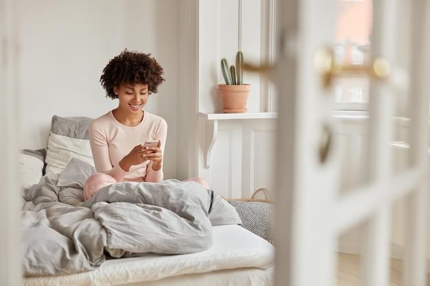 Positieve donkere vrouw leest internetpublicatie op website via mobiele telefoon