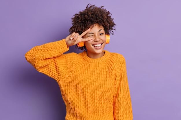 Positieve donkere vrouw maakt vredesgebaar over oog glimlacht breed heeft plezier voelt zich geamuseerd luistert aangenaam liedje in koptelefoon poses