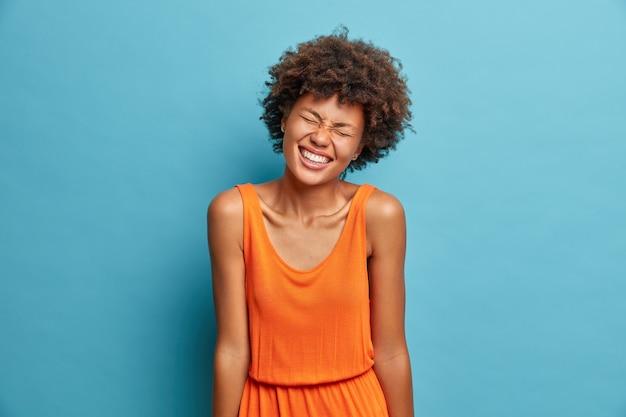 Positieve donkere vrouw met een dolgelukkige uitdrukking sluit de ogen en lacht