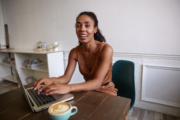 Positieve donkere vrouw met krullend haar die op afstand in koffiehuis werkt, haar handen op de sleutel houdt en vreugdevol kijkt
