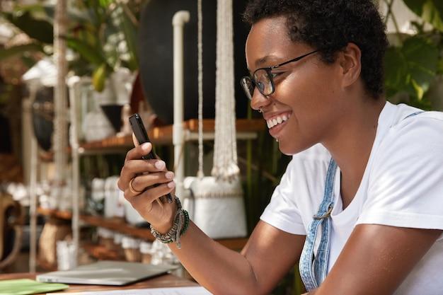 Positieve donkere vrouw opgewonden met goed nieuws krijgen melding op slimme telefoon