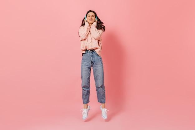 Positieve donkerharige meisje lacht tijdens het luisteren naar muziek in blauwe koptelefoon. vrouw in gebreide outfit en witte sneakers springen op roze achtergrond.