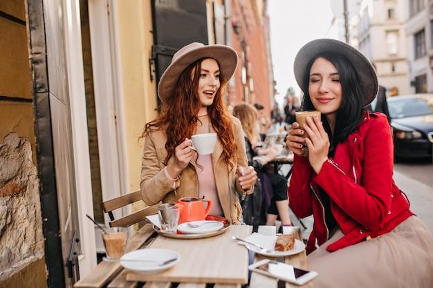Positieve donkerharige vrouw in rode jas genieten van koffie met gesloten ogen met haar vriend