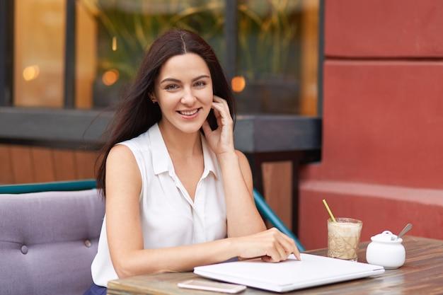 Positieve donkerharige vrouw in witte outfit, omringd door moderne gadgets, zit in de coffeeshop, lacht zachtjes naar de camera, heeft een goed humeur, wacht op bestelling en gaat na het werk lunchen.