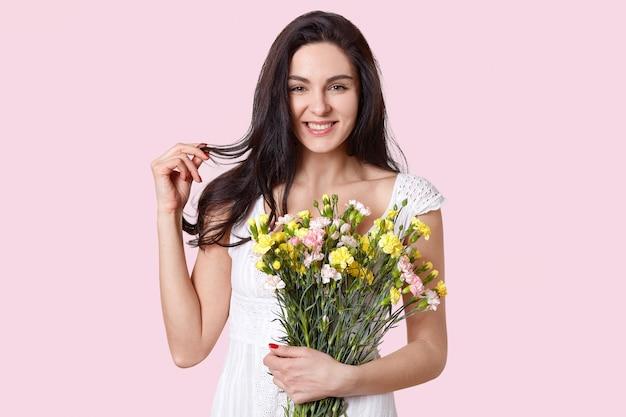 Positieve donkerharige vrouw raakt haar aan, lacht zachtjes, heeft een aantrekkelijke uitstraling, heeft eerste lentebloemen, heeft rode manicure, gekleed in een witte jurk, geïsoleerd op roze. schoonheid concept