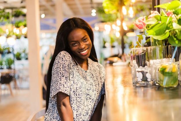 Positieve donkerhuidige vrouw van gemengd ras geniet van een goede nachtrust in de coffeeshop