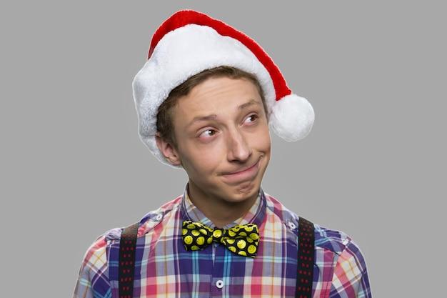 Positieve doordachte tienerjongen in kerstmuts. de tienerjongen in kerstmanhoed denkt over gift. kerst vakantie concept.