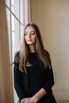 Positieve elegante jonge vrouw in zwarte slijtage in kamer