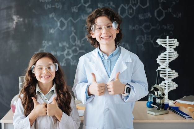 Positieve emoties delen. glimlachende blije kleine wetenschappers die in het laboratorium staan terwijl ze aan het project werken en hun duimen laten zien