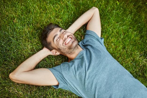 Positieve emoties. jonge mooie bebaarde blanke man in blauw t-shirt liggend op gras lachend met tanden, lachen, ontspannen buiten in zomerochtend met blij gezicht expressie.