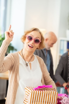 Positieve emoties. leuke gelukkige vrouw die met haar vinger omhoog wijst terwijl ze een geschenkdoos vasthoudt