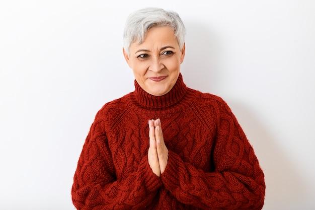 Positieve emoties, reacties en gevoelens. portret van aantrekkelijke vrolijke oudere senior dame met kort grijs kapsel gaat in lachen uitbarsten, in goed humeur zijn, hand in hand in namaste
