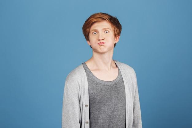 Positieve emoties. sluit omhoog portret van jonge knappe gemberkerel in modieus grijs t-shirt onder toevallig vest met dwaze gezichtsuitdrukking, hebbend pret.