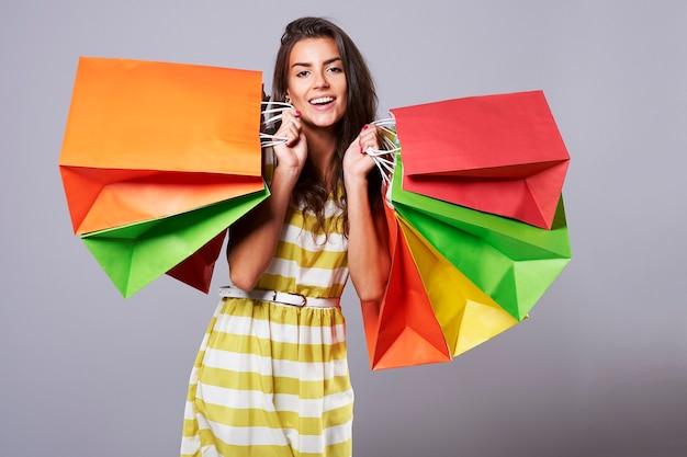 Positieve emoties van vrouw met kleurrijke boodschappentassen