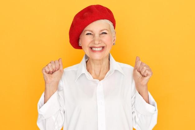 Positieve emoties, viering, vreugde en geluk concept. studio foto van extatische dolgelukkig volwassen vrouw in stijlvolle rode motorkap opgewonden uitroepen, gebalde vuisten, goed nieuws of succes vieren