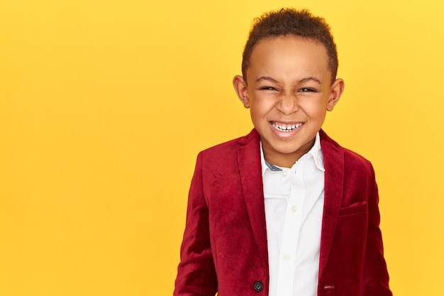 Positieve emoties, vreugde en een gelukkig jeugdconcept. knappe vrolijke donkere huid mannelijk kind in karmozijnrode fluwelen jasje in goed humeur, camera kijken met stralende glimlach, witte tanden tonen