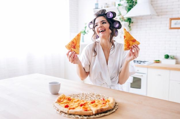 Positieve emotionele jonge zorgeloze huishoudster in keuken. houd twee plakjes pizza en glimlach. cup op tafel. alleen in de keuken. leven zonder werk.