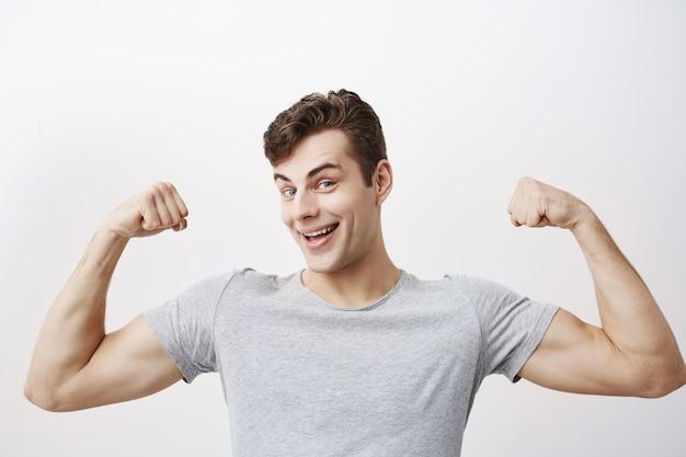Positieve emotionele man glimlacht, toont spieren op zijn armen, voelt zich trots sterk en sterk te zijn, zegt: ik ben held. gespierde mannelijke atleet steekt de armen van vreugde op, laat zien hoe sterk hij is.