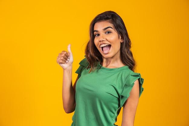 Positieve en gelukkige jonge vrouw met omhoog duim.