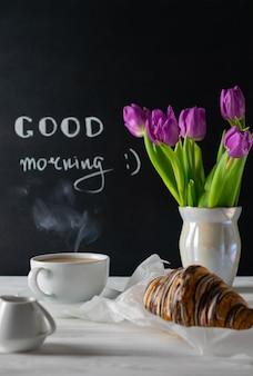 Positieve en gelukkige ontbijtomgeving met tulpenboeket, koffie en croissant
