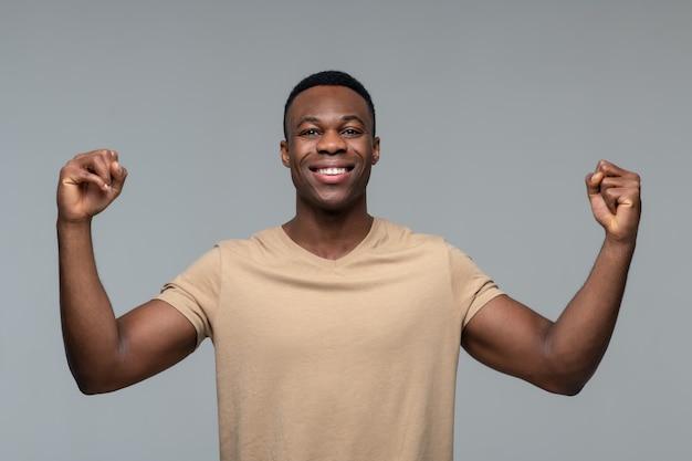 Positieve energie. jonge volwassen knappe donkerhuidige man die lacht met gespierde armen die vuisten opheffen op vlak gezicht