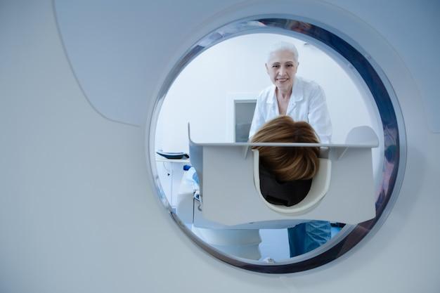 Positieve ervaren senior arts die zich in de buurt van haar patiënt bevindt en naar haar kijkt terwijl de diagnostiek wordt gestart