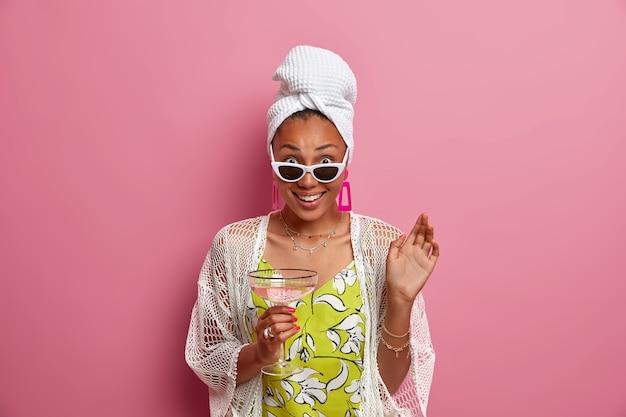 Positieve etnische dame kijkt van onder een zonnebril houdt een glas martini-cocktail vast en draagt huishoudelijke kleding en brengt vrije tijd door op een binnenlands feest geïsoleerd over roze muur. mensen levensstijl concept